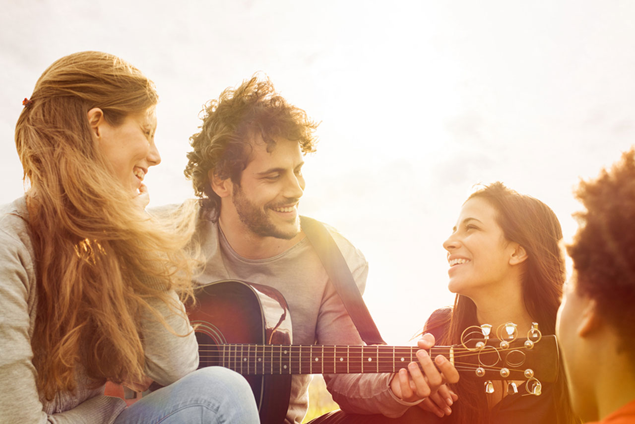 Four people sitting around a man playing a guitar. The sun is setting behind them.