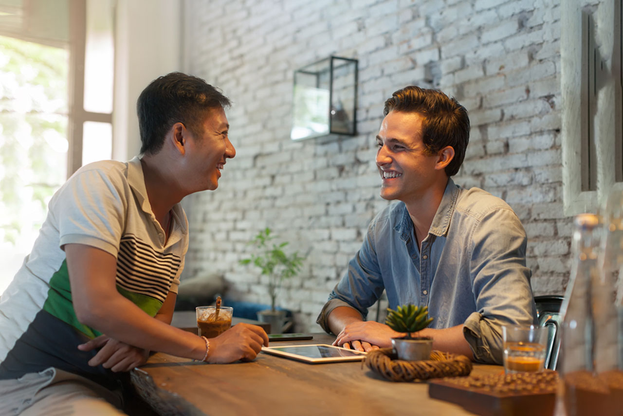 A man of Asian descent sits at a restaurant table with a man with white skin. They are both looking at each other and smiling.