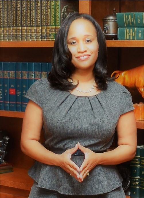 Black woman with dark hair and grey suit standing in front of bookshelves, hands clasped together